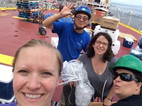 The University of Manitoba team during cruise mobilization on deck of the Amundsen in Québec City, Québec. Alexis Burt, Kang Wang, Deb Armstrong, and Kathleen Munson (left to right) unpack boxes and install equipment. Photo: Alexis Burt.